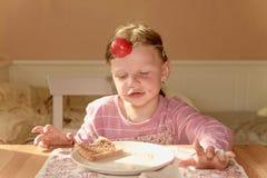 Girll ребенк ест сливк шоколада распространенную на хлебе Закуска еды шоколада сладостная Счастливая девушка имеет закуску в кухн Стоковые Фото