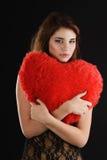 Girll adolescente con la almohada del corazón Imagenes de archivo