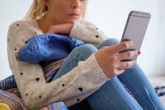 Girll adolescente joven con el teléfono en su cama Imagenes de archivo