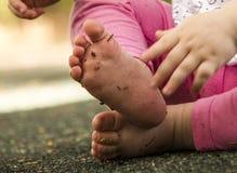 Girll do bebê com pé sujo no campo de jogos exterior do verão Fotografia de Stock