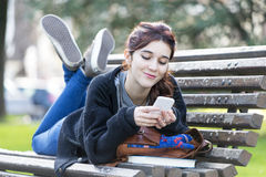 Girll looking message on phone, feeling and emotion lifestile co. Hipster hapiness young woman lying on the old wood bench looking message on smart phone in the Stock Photo
