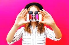 Girll que toma el autorretrato de la imagen en smartphone sobre colorido Foto de archivo libre de regalías