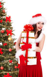 Girll in santa hat and fir tree with gift box. Stock Images