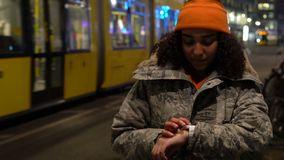 Girll young woman using smart watch at night with trams by Alexanderplatz Station, Berlin, Germany. Beautiful mixed race female teenager girl young woman wearing stock video
