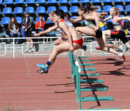 Girls on the 100 meters hurdles race Stock Photos