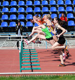 Girls on the 100 meters hurdles race Stock Image