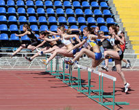 Girls on the 100 meters hurdles race Stock Photography