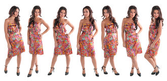 Girls. Seven identical girls of models in a coloured dress pose on a white background royalty free stock image