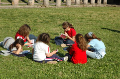 Girls. Six girls sitting in a circle and reading books stock image