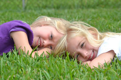 Girls. Two little girls lying in the grass Royalty Free Stock Photos