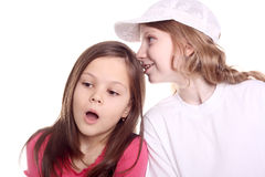 Girls. Cute little girl whispering a secret to her friend Stock Photos