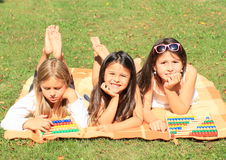 Girls with abacuses. Three lying little barefoot girl playing with two colorful abacuses Stock Photos