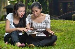 Girls Activity reading magazine outdoor Stock Photography