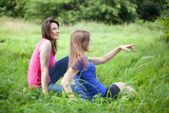Girls admire the view. On a green glade stock images