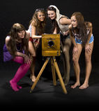 Girls admiring antique camera. A studio view of four teenage girls looking at and admiring an antique, wooden camera.  Black background Stock Photography