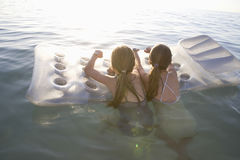 Girls On Air Mattress Floating On Water Royalty Free Stock Image
