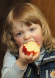 Girls with apple. Girls eats red apple one royalty free stock photos
