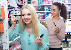 Girls applying mascara near mirror Royalty Free Stock Image