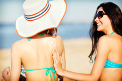 Girls applying sun cream on the beach Stock Photos
