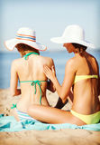 Girls applying sun cream on the beach Stock Photo
