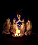 Girls in aprons by campfire. Teenage girls wearing aprons and holding cooking utensils around a campfire.  Isolated against a black background Stock Image