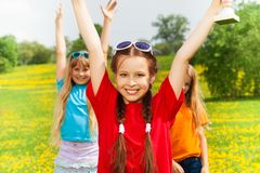 Girls with award. Closeup of happy girl with prize cup award with her friends jumping on background stock image