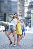 Girls are back in town. Lovely young women having fun in the city streets Stock Image