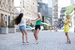 Girls are back in town. Lovely young women having fun in the city streets Royalty Free Stock Images