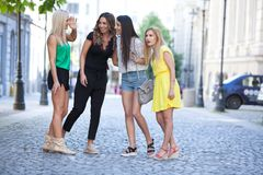 Girls are back in town. Lovely young women having fun in the city streets Royalty Free Stock Image
