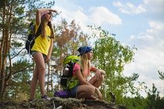 Girls with backpack in hill forest. Adventure, travel, tourism concept. Teenage girls traveling with backpack climb in hill forest. Adventure, travel, tourism Stock Photography
