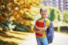 Girls with backpack. Pupil of primary school with book in hand. Girl with backpack near building outdoors. Beginning of lessons. First day of fall stock photography