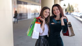 Girls with a bags walking in a city center. Portrait young hipster girls with shopping bags walking in a city center stock video