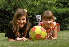 Girls with the ball 1. Two cute smiling girl with the ball lying on the grass stock image