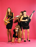 Girls band. With musical instruments in elegant black dresses over pink Royalty Free Stock Images
