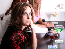 Girls At The Bar. Three girls sitting at a bar with drinks.  Girl in foreground has a professional makeup application Royalty Free Stock Photo