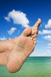 Girls barefoot feet on the sandy beach Royalty Free Stock Image