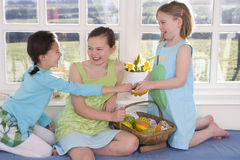 Girls with basket of wooden Easter eggs Royalty Free Stock Image