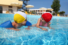 Girls bath in pool near skirting on rest Stock Photos