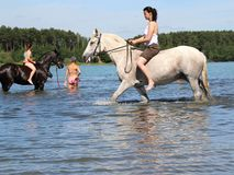 Girls bathe horse in the lake. Stock Photos