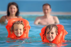 Girls bathing in lifejackets with parents in pool. Two little girls bathing in lifejackets with parents in pool on a resort royalty free stock photography