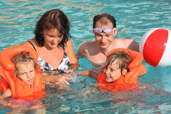 Girls bathing in lifejackets with parents in pool Stock Photography