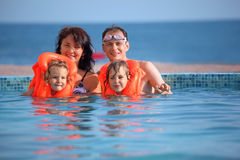Girls bathing in lifejackets with parents in pool Stock Images