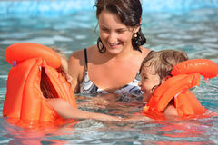 Girls bathing in lifejackets with woman in pool. Two little girls bathing in lifejackets with young woman in pool on resort, Looking against each other stock image