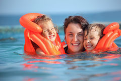 Girls bathing in lifejackets with woman in pool. Two little girls bathing in lifejackets with young woman in pool on resort stock images