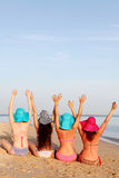 Girls in bathing suits sit back on the beach Stock Image