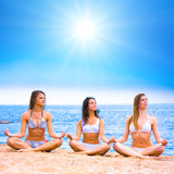 Girls on a beach. Girls doing yoga on a beach Royalty Free Stock Image