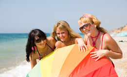 Girls on the beach. Three girls with colored parasol are posing on seashore looking at camera smiling Royalty Free Stock Images