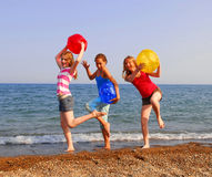 Girls on a beach. Three girls on a sandy beach being silly with colorful balls Stock Images