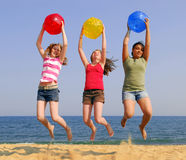 Girls on a beach. Three girls on a sandy beach jumping with colorful balls Stock Photography