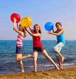Girls on beach. Three girls with colorful beach balls walking on sea shore Royalty Free Stock Photos